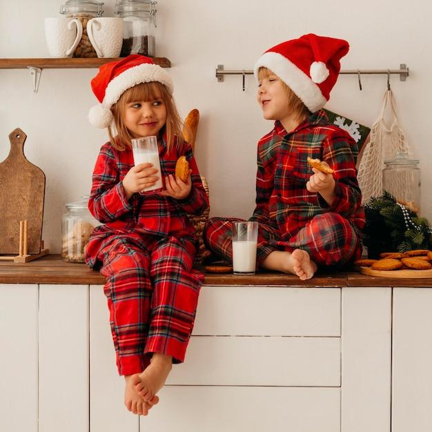 Милые дети едят рождественское печенье и пьют молоко Бесплатные Фотографии