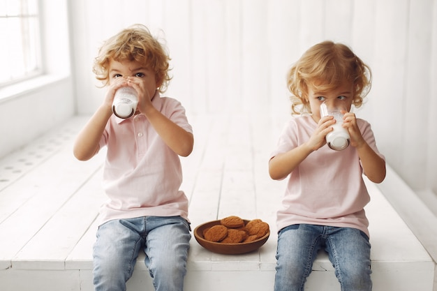 Cute children eating cookies and drinking milk Free Photo