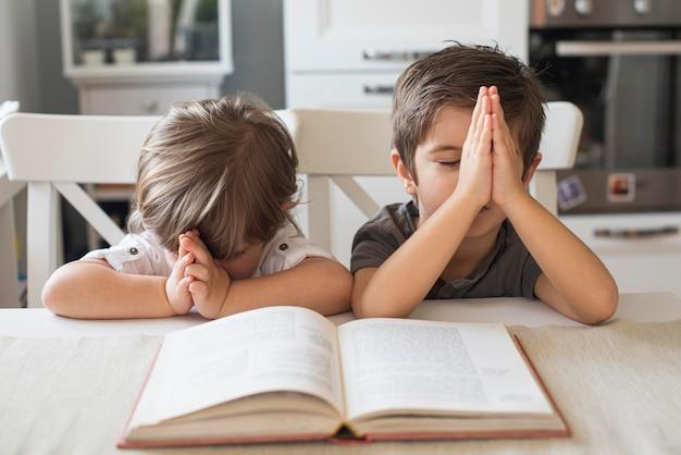 Cute children praying together at home Premium Photo
