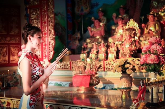 Premium Photo | Cute chinese girl dressing traditional cheongsam suit  burning incense sticks and pay respect and praying to chinese god for luck