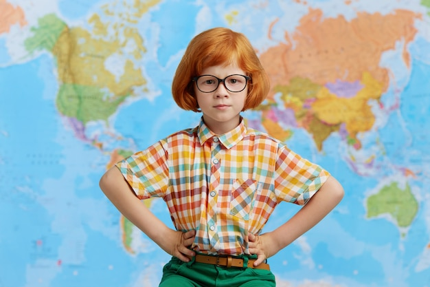Ragazzino sveglio sveglio con gli occhiali d'uso dell'acconciatura di bob dello zenzero che si tengono per mano sulla sua vita, posante contro la mappa di mondo. infanzia, apprendimento e istruzione Foto Gratuite