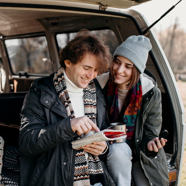 Cute couple checking a map while having a road trip Free Photo