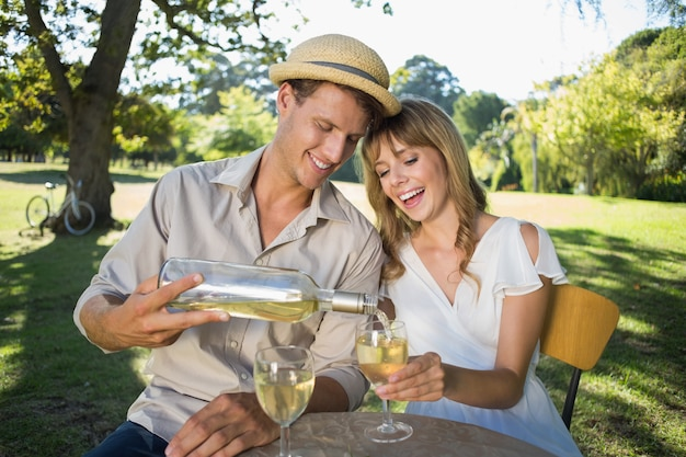 Cute couple drinking white wine together outside Premium Photo