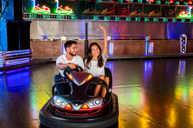 Cute couple having fun in bumper cars Free Photo