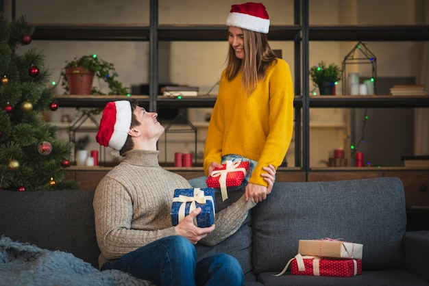 Cute couple holding gifts in living room Free Photo