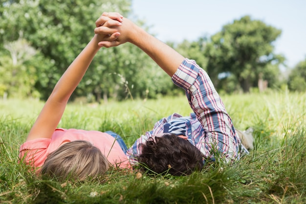 Cute couple holding hands in the park on a sunny day Premium Photo