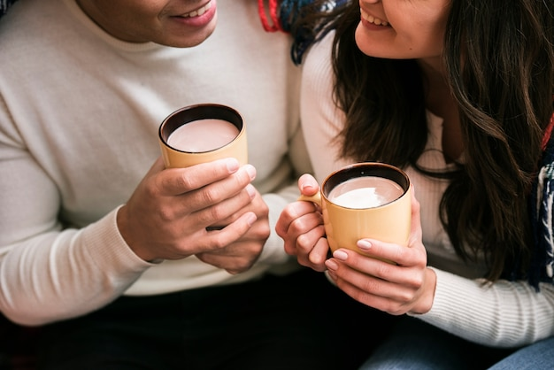 Cute couple holding hot drinks Free Photo