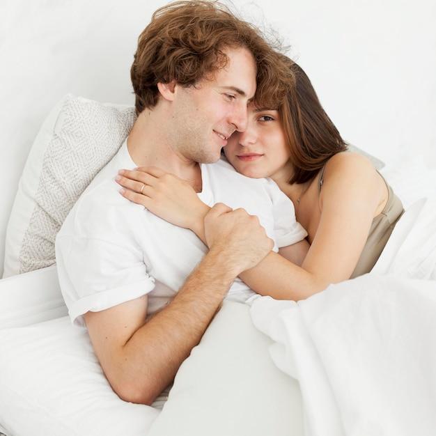 Cute couple hugging in bed medium shot Free Photo