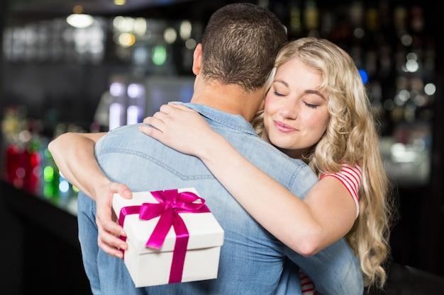 Милая пара обниматься с подарком Premium Фотографии