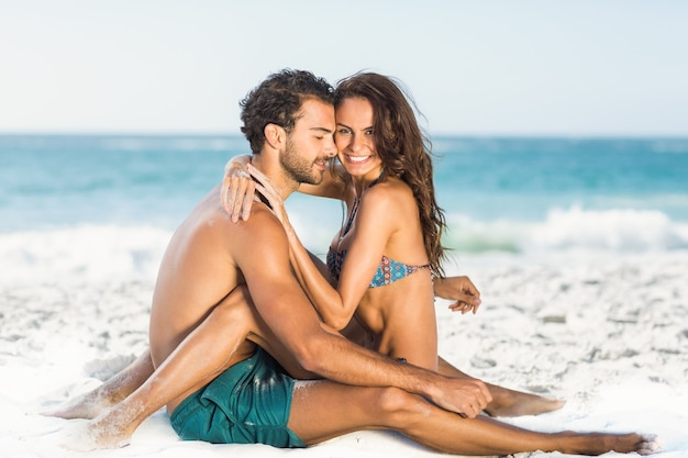 Милая пара обниматься, сидя на пляже Premium Фотографии