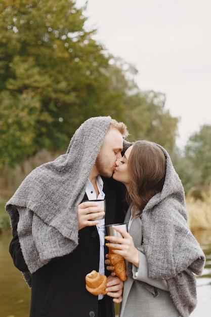 Милая пара в парке. дама в сером пальто. люди с термосом и круассаном. Бесплатные Фотографии