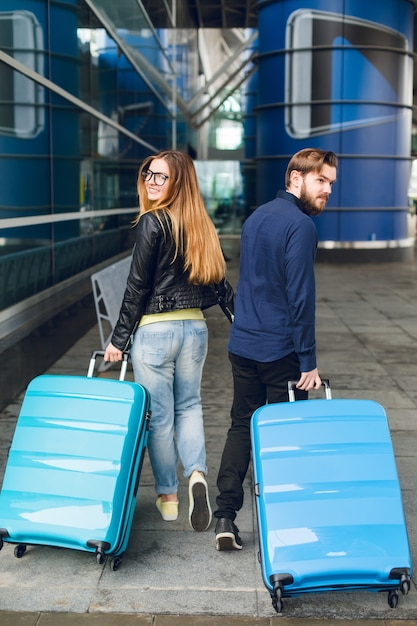 Coppia carina sta camminando con le valigie fuori in aeroporto. ha capelli lunghi, occhiali, maglione giallo, giacca. indossa camicia nera, barba. vista dal retro. Foto Gratuite