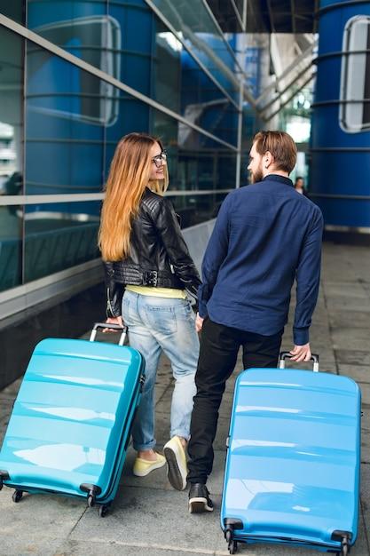かわいいカップルが空港で外のスーツケースで歩いています。彼女は長い髪、メガネ、黄色いセーター、ジャケットを持っています。彼は黒いシャツ、ひげを着ています。彼らは手をつないで笑っています。後ろから見たところ。 無料写真