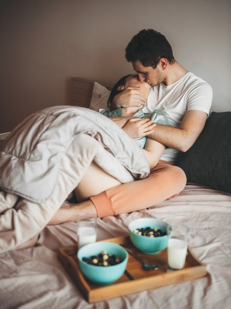 Милая пара целуется в постели в пижаме перед едой хлопьев с молоком Premium Фотографии
