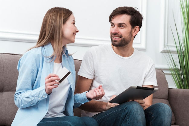 Cute couple looking at each other and holding digital devices for online purchases Free Photo