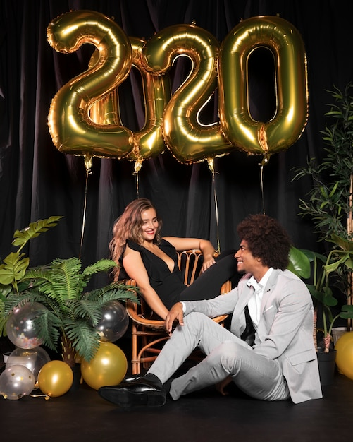 Cute couple looking at each other surrounded by balloons with 2020 new year Free Photo