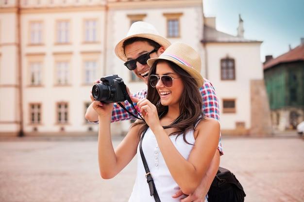 Coppia carina alla ricerca sulle loro foto sulla fotocamera Foto Gratuite