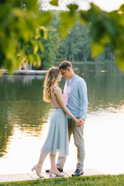 Cute couple in love, closing their eyes and touching their foreheads while walking near the lake Premium Photo