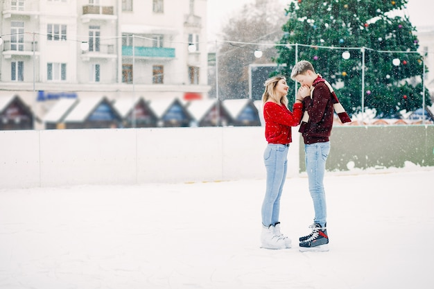 Cute couple in a red sweaters having fun in a ice arena Free Photo