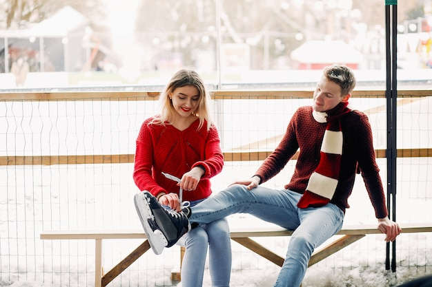 Cute couple in a red sweaters help each other to skate Free Photo