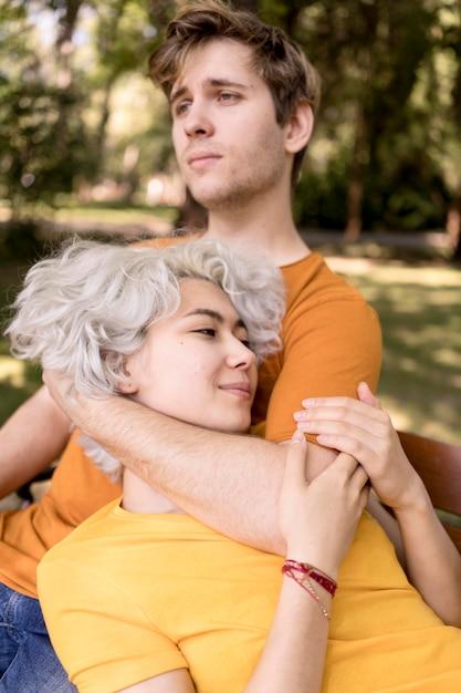 Coppia carina rilassante insieme sulla panchina mentre fuori nel parco Foto Gratuite