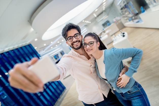 자기 초상화를 복용 하 고 기술 저장소에 서있는 동안 포옹하는 귀여운 커플. 새로운 기술 개념. 프리미엄 사진