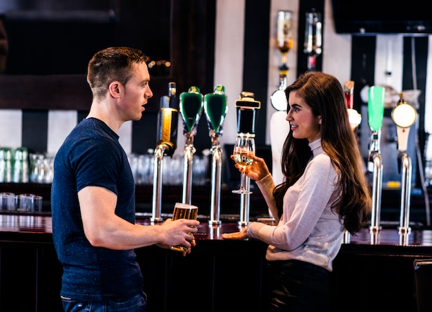 Cute couple talking and having a drink in a bar Premium Photo