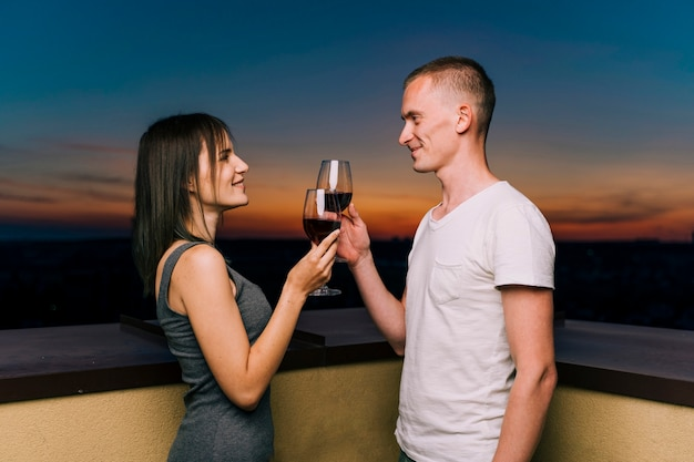 Cute couple toasting wine on rooftop Free Photo
