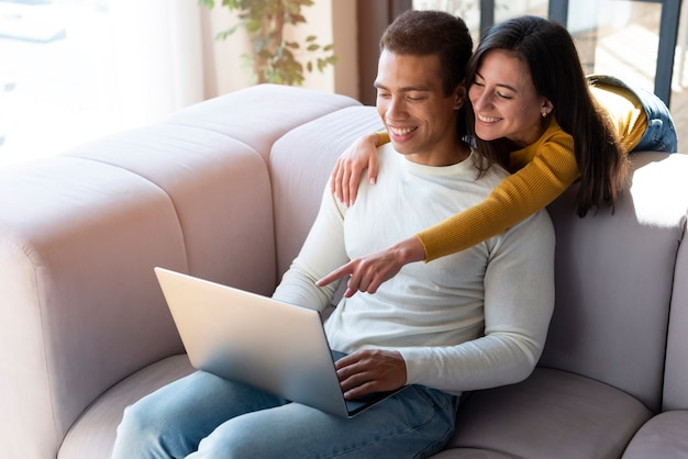 Cute couple using a laptop together Free Photo