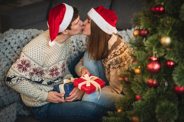 Cute couple with christmas gifts kissing Free Photo