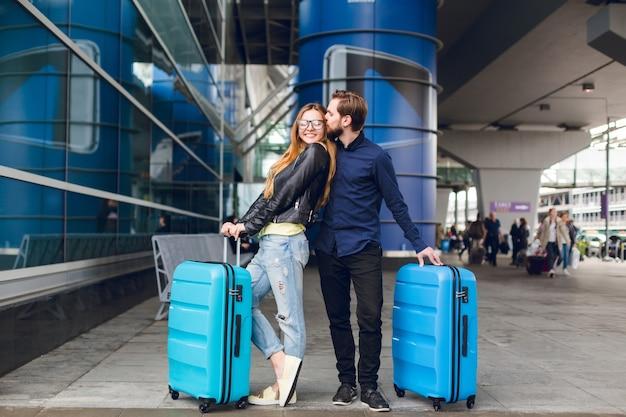 Coppia carina con le valigie è in piedi fuori in aeroporto. ha capelli lunghi, occhiali, maglione giallo, giacca. indossa camicia nera, barba. il ragazzo sta abbracciando e baciando la ragazza. Foto Gratuite