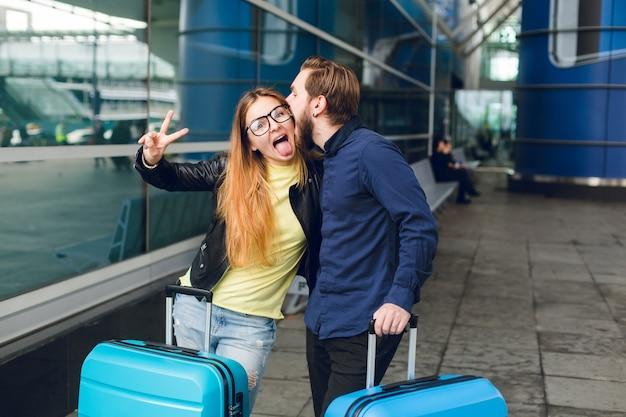 Coppia carina con valigie è in piedi fuori in aeroporto. ha capelli lunghi, occhiali, maglione giallo, giacca. indossa camicia nera, barba. si stanno abbracciando e scimmiottando insieme. Foto Gratuite