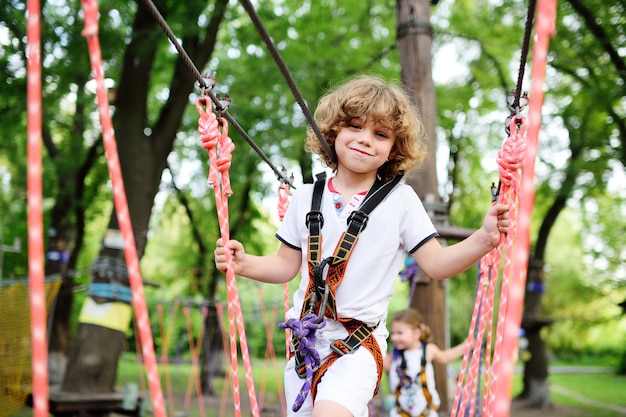 Cute curly child in a rope park Premium Photo