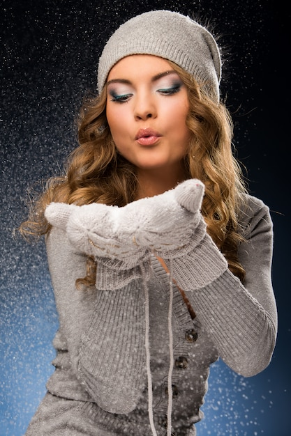 Cute curly girl wearing mittens during snowfall Free Photo