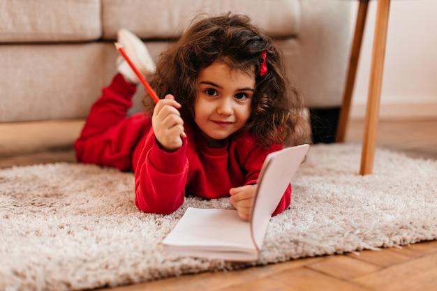 Симпатичный темноглазый ребенок, лежащий на ковре. очаровательный ребенок с ноутбуком, глядя на камеру. Бесплатные Фотографии