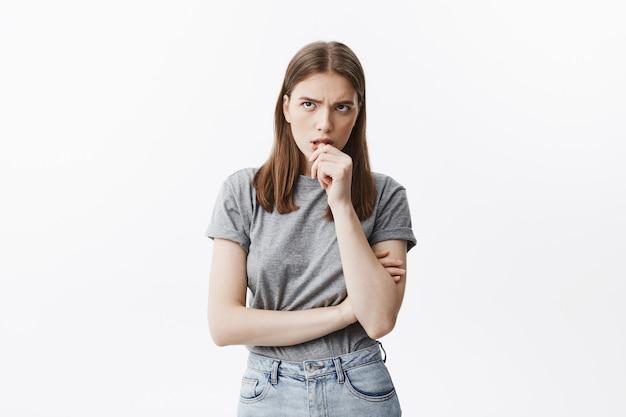 灰色のtシャツを着たかわいい黒髪の不幸な学生少女は、興奮した表情で脇をよそ見しながら、大学でのテスト結果を待ってリラックスできません。 無料写真