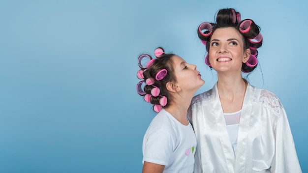 Cute daughter kissing mother in curlers and bathrobe Free Photo