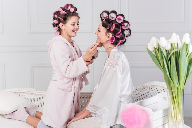 Cute daughter putting powder on mothers neck Free Photo