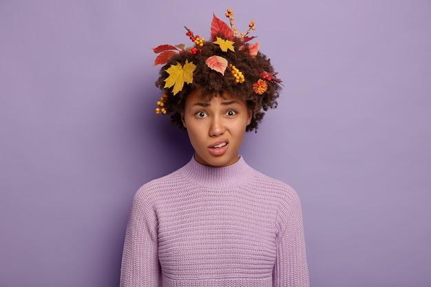 La carina signora afroamericana insoddisfatta sorride, porta le labbra, ha l'espressione del viso triste, indossa foglie gialle e bacche in un maglione lavorato a maglia isolato su viola. Foto Gratuite