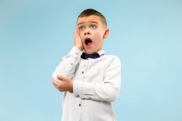Ragazzo teenager elegante sveglio su priorità bassa blu. espressione emotiva Foto Gratuite