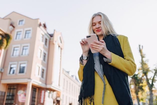 Carina donna bionda attraente emotiva in cappotto con smartphone cammina per la strada della città Foto Gratuite