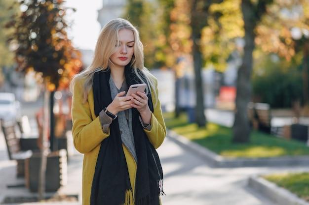 스마트 폰 코트에 귀여운 감정적 매력적인 금발의 여자는 도시 거리를 산책 무료 사진