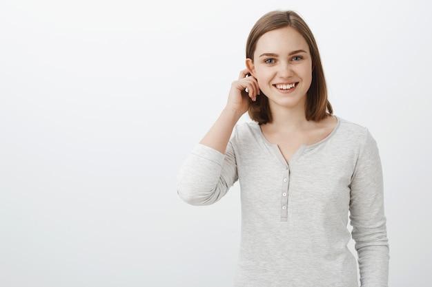 カジュアルなブラウスのかわいい感情的な10代の少女の耳たぶの後ろで髪をフリックし、白い壁を越えて興味深い会社と一緒に遊ぶように誘われて恥ずかしがり屋とうれしそうに広く笑って 無料写真