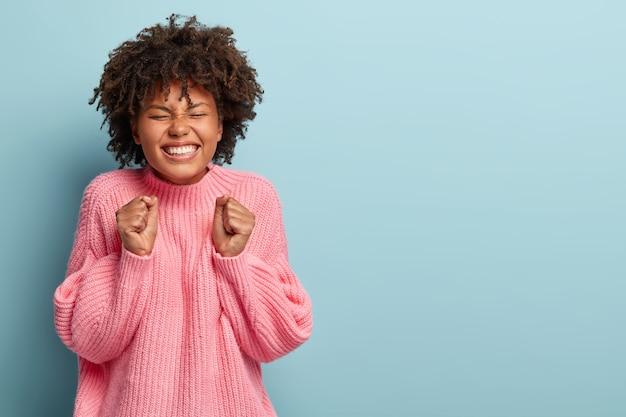 Carina donna emotiva felice di raggiungere l'obiettivo e ottenere un buon risultato, stringe i pugni, sorride felice Foto Gratuite