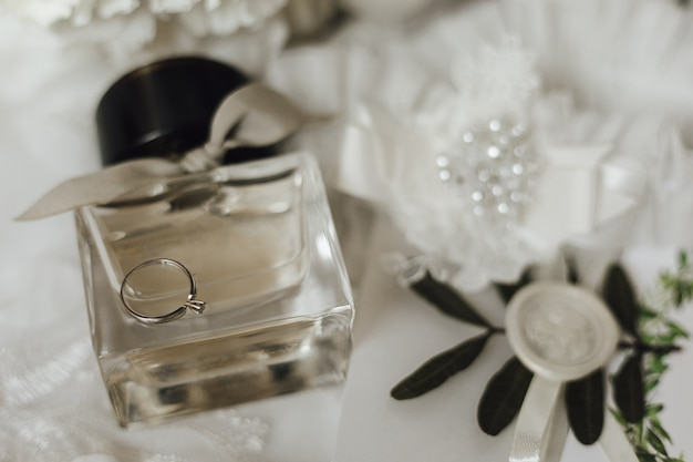 Cute engagement ring made of white gold with diamond on the glass bottle of perfume Free Photo