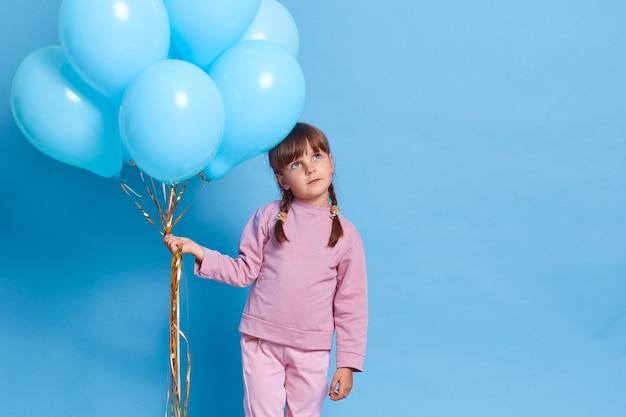 장미 닫는 귀여운 유럽 여자 아이, 사려 깊은 표정으로 길을 찾고 땋은 아이, 파란색 벽에 헬륨 풍선 무리를 들고 즐거운 무언가에 대한 꿈. 무료 사진