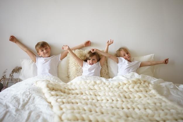 Симпатичные европейские братья и сестры наслаждаются медленным ленивым утром, растягиваясь в спальне родителей. трое очаровательных небрежно одетых детей бездельничают в спальне, протягивая руки и не желая вставать Бесплатные Фотографии