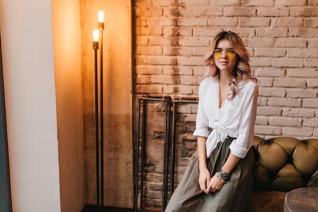Симпатичная светловолосая девушка в белой рубашке сидит на кожаном диване в комнате с дизайном лофт и смотрит с интересом Бесплатные Фотографии