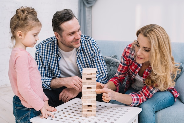 Cute family playing wooden block game tower at home Free Photo