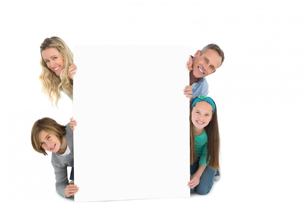 Cute family smiling at camera holding poster Premium Photo